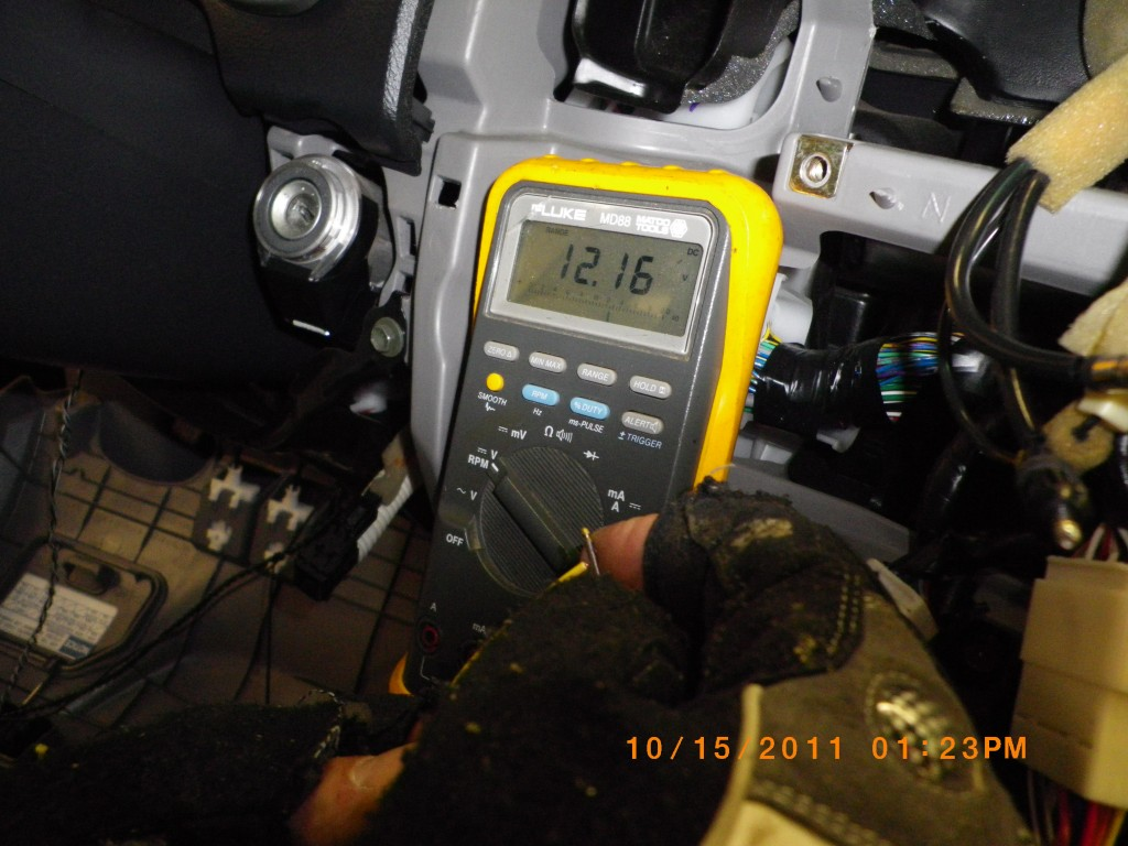 Using a multimeter to test stock stereo harness wires.